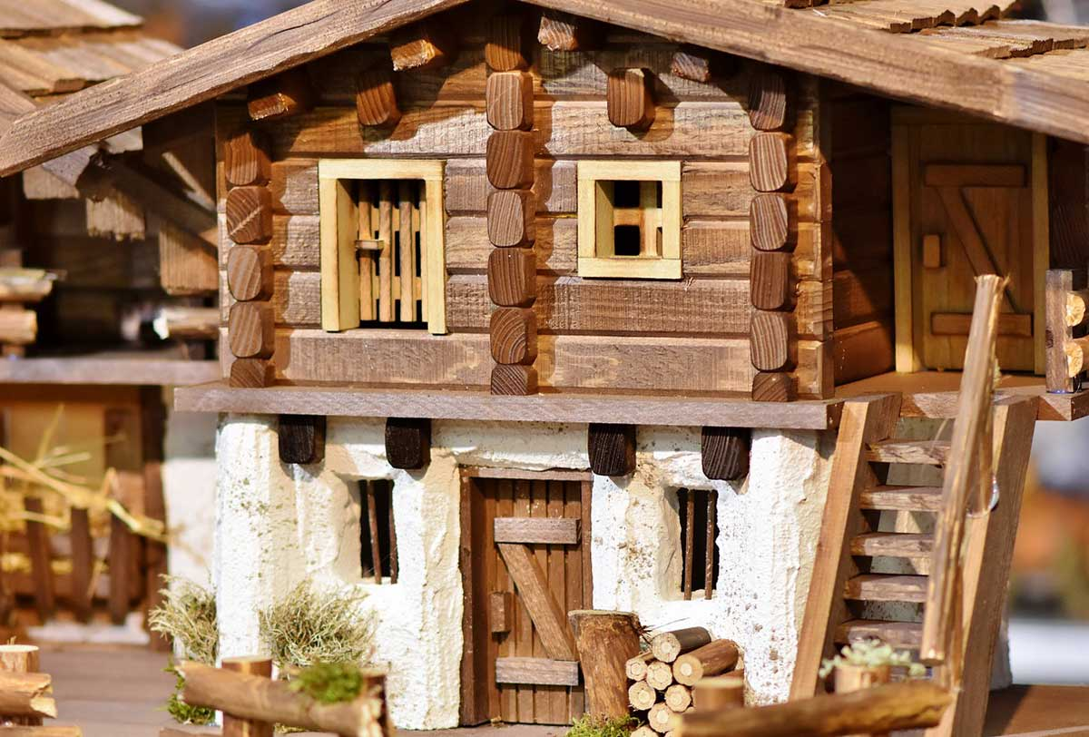 A model wooden house with a rack of logs by the front door and stairs to the upper floor.