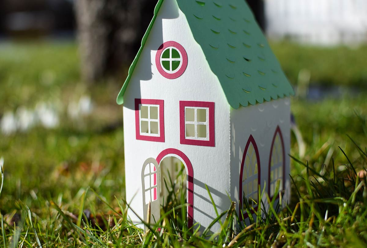 A model house made of card, placed outside on the lawn.