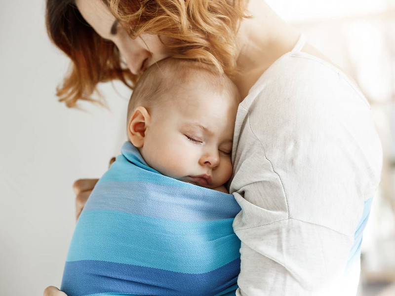 Mum cuddling her baby who is in a blue baby sling.