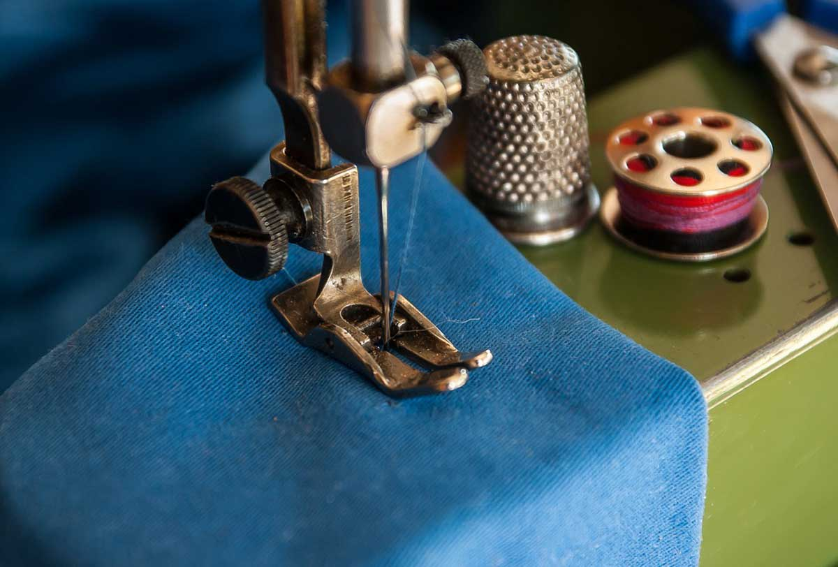Blue material being stitched in the sewing machine with blue thread.