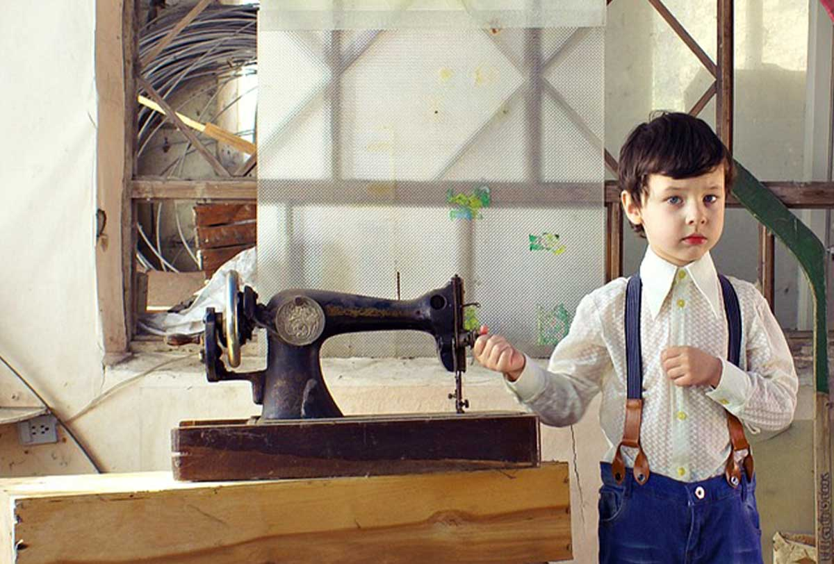Young boy standing next to an old-fashioned sewing machine.