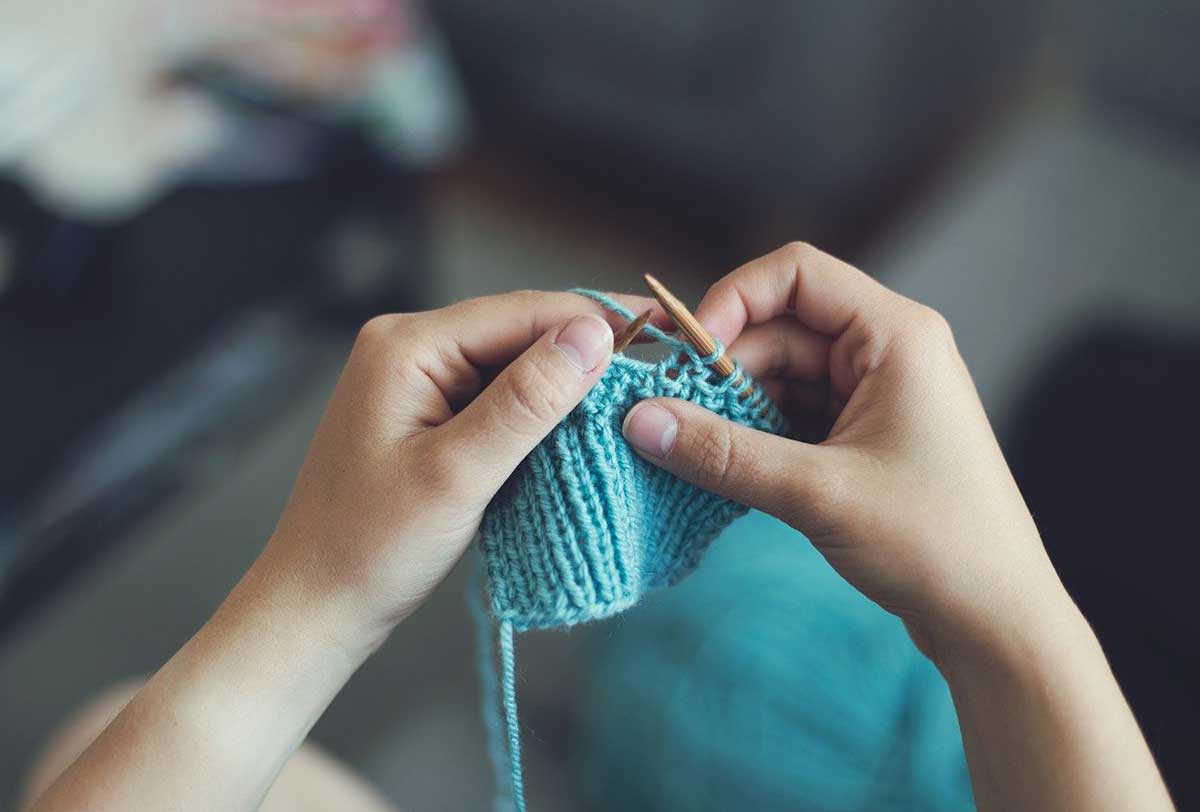Young boy knitting with blue string.
