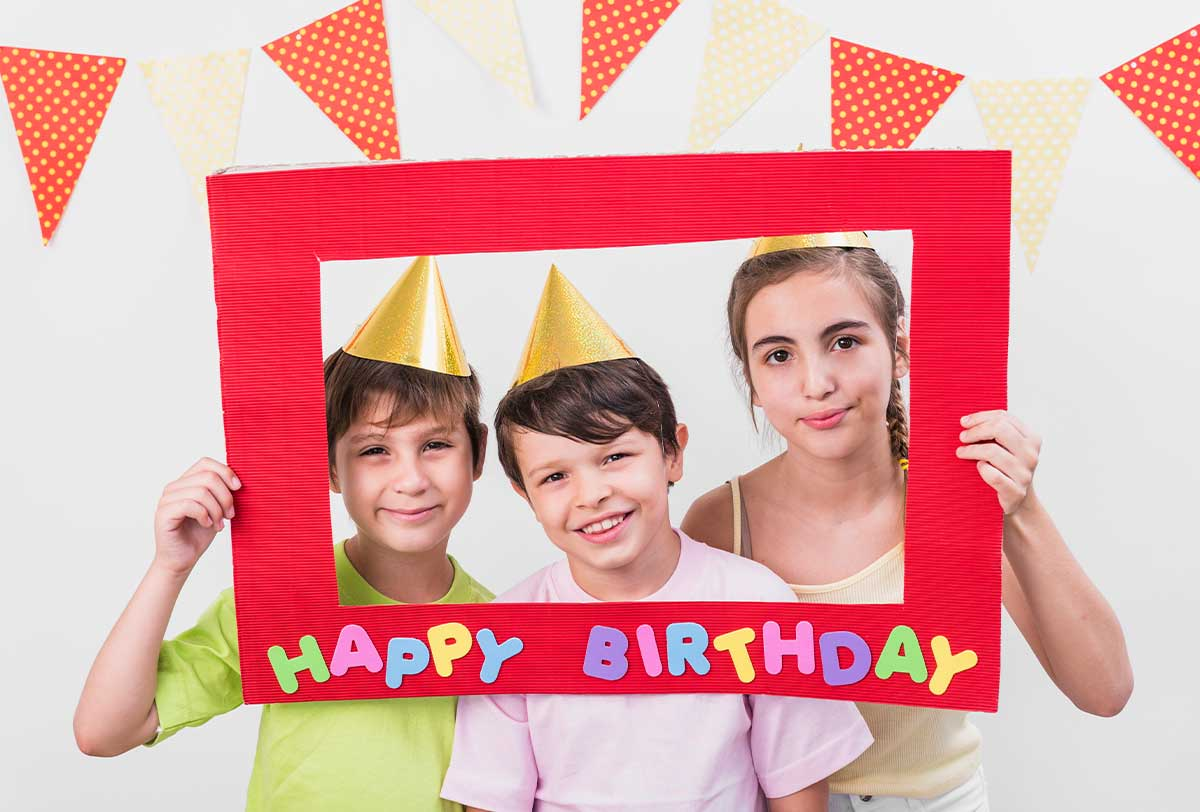 Three kids holding up a birthday banner frame and standing with their faces inside.