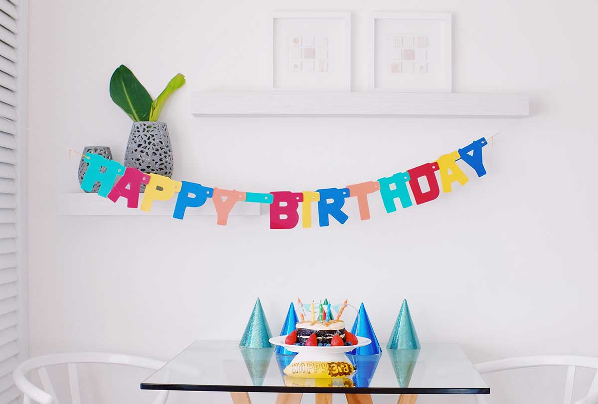 Happy birthday spelled out in a banner hanging on the wall behind a table with a cake and party hats on it.