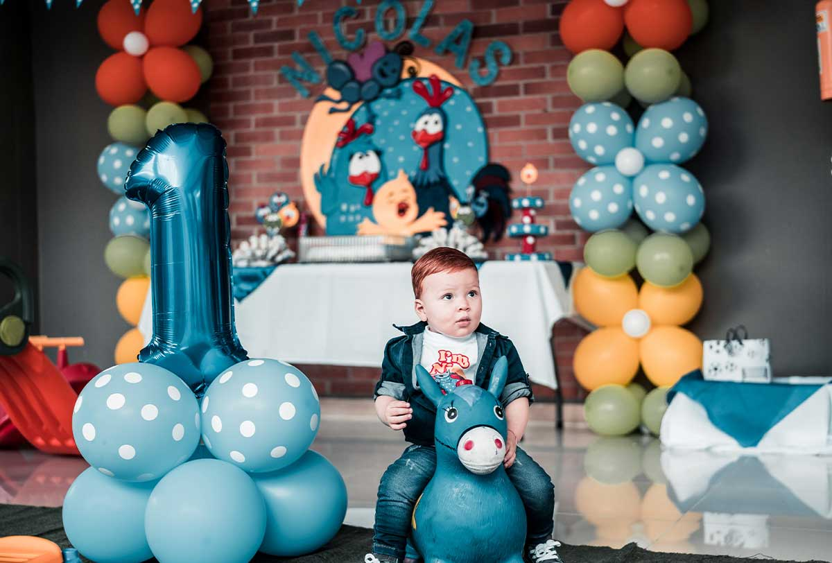 Toddler sat on a toy donkey at his first birthday party with balloon banners decorating.