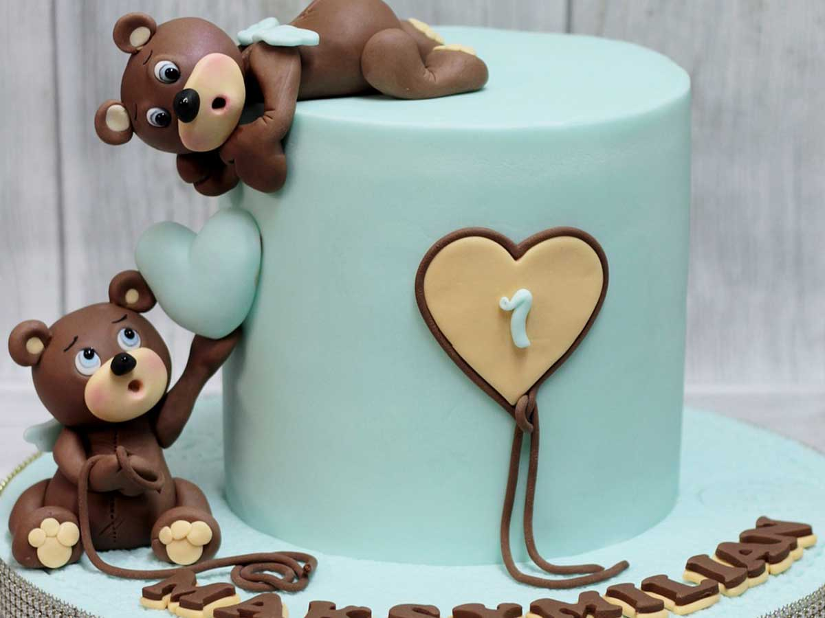 A mint green first birthday cake with two bears made from fondant icing passing an icing heart to each other on the cake.