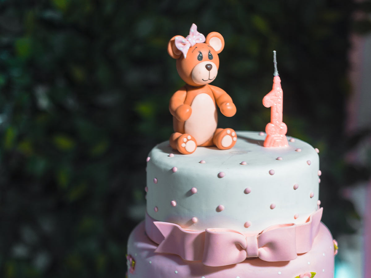 A tiered, pastel-coloured cake with an icing bear sat on the top.