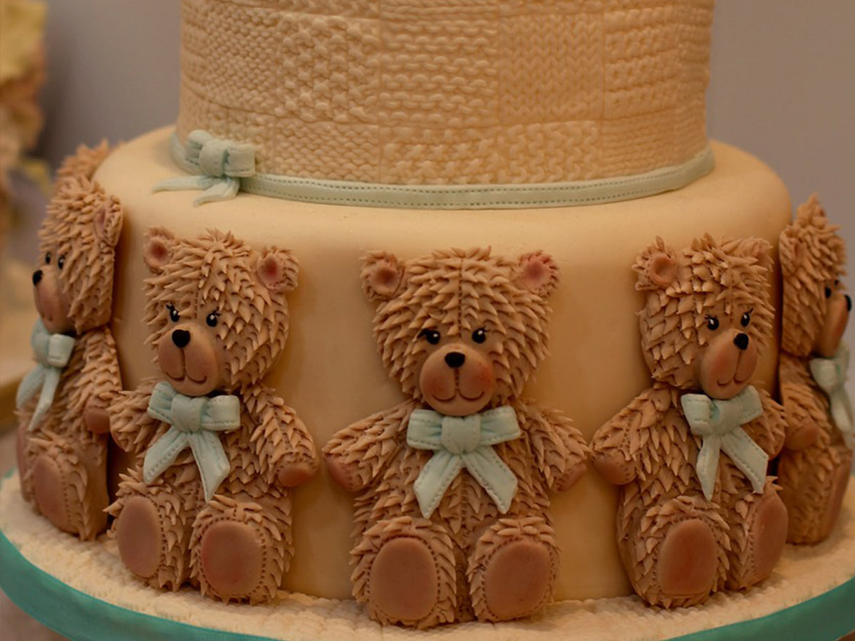 Tiered cake with brown icing bears going all around the bottom tier.