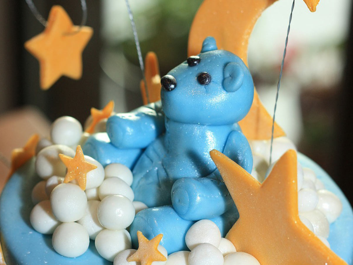 A bear made from blue icing sitting on top of a blue cake with icings stars and moons.