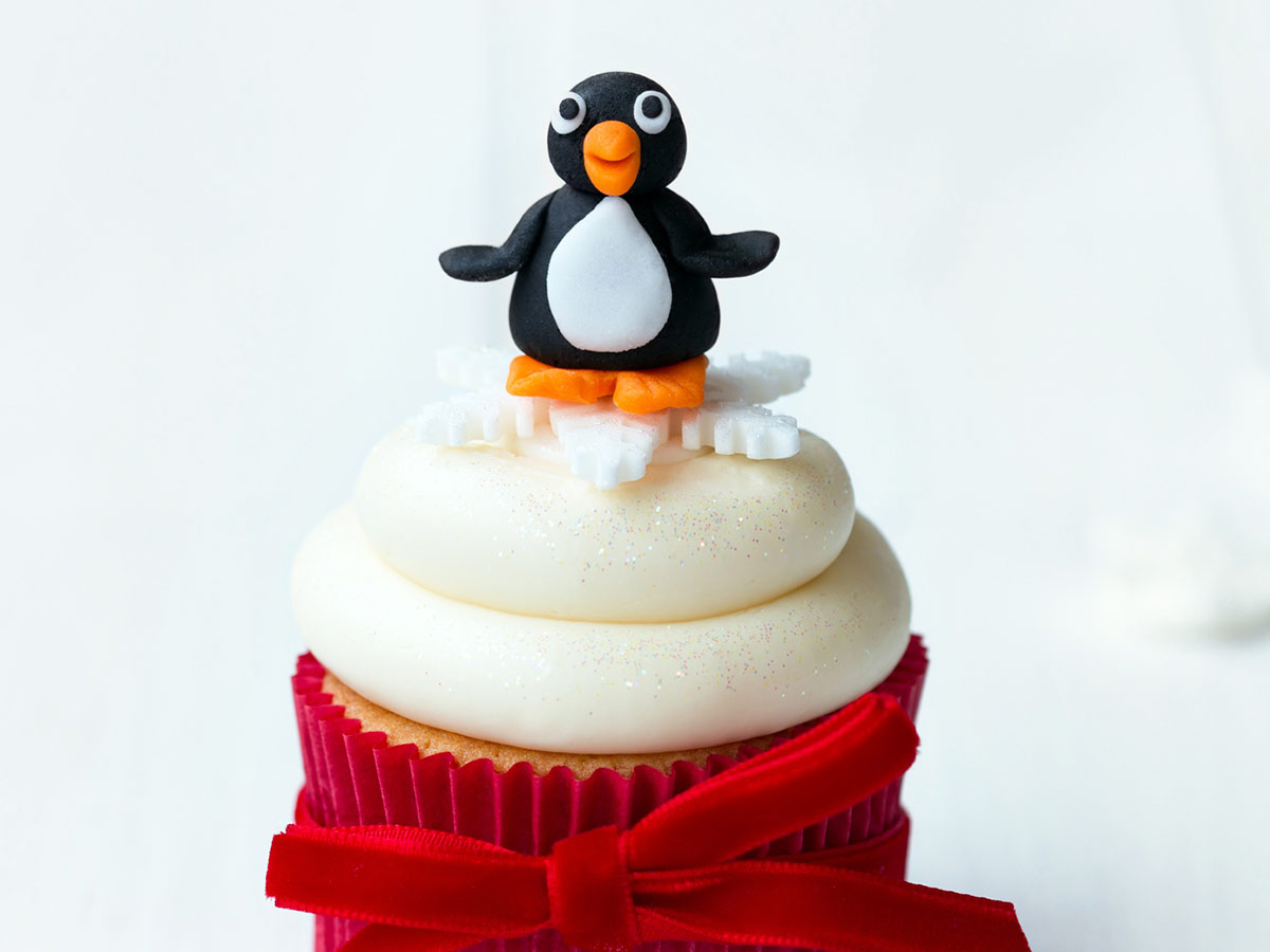 A cupcake in a red case with white frosting and an icing penguin figure on top.