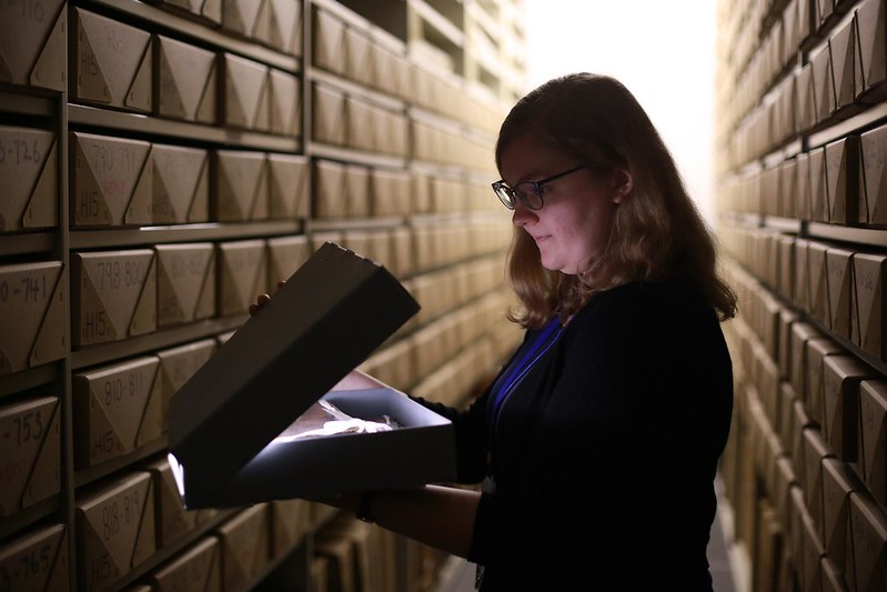 Woman opening box in archives at Bank of England Museum.