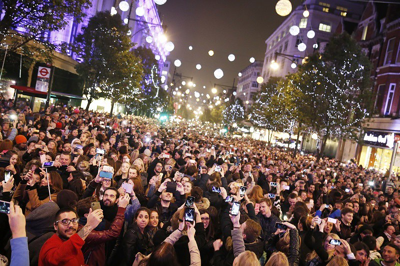 Crowds of people gathered to see Oxford Street Christmas lights at night.