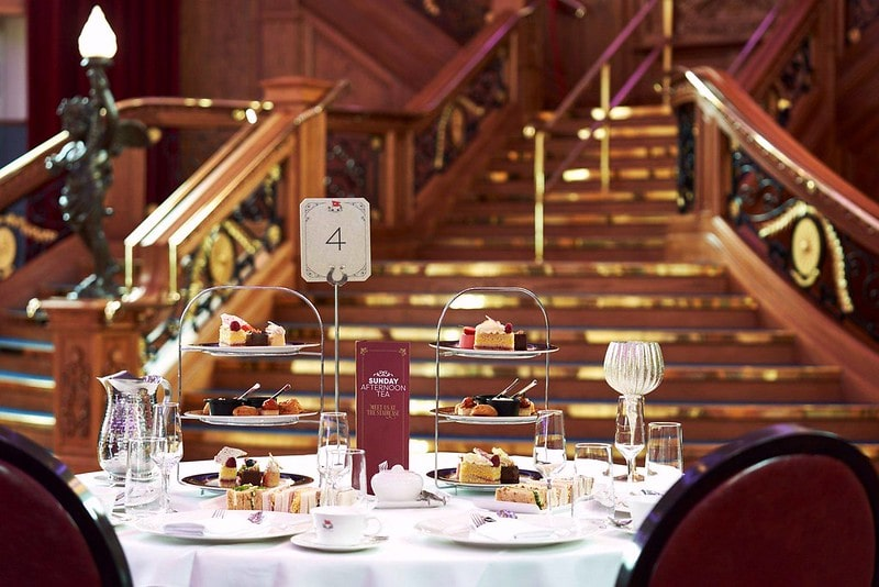 A table setting filled with sandwiches, savoury items, scones and cakes, positioned by the Grand Staircase at the Titanic Belfast.