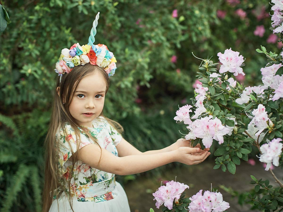 Little girl wearing a DIY unicorn horn as she reaches for some flowers in the garden.