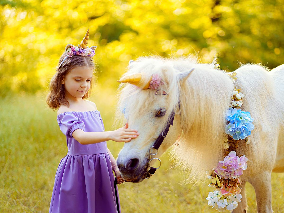 Young girl in a purple dress and DIY unicorn horn petting a white pony who is also wearing a unicorn horn.