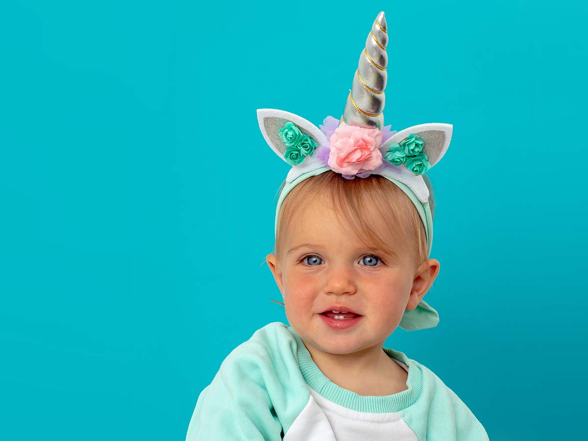Toddler sat in front of a blue background wearing a DIY unicorn horn.