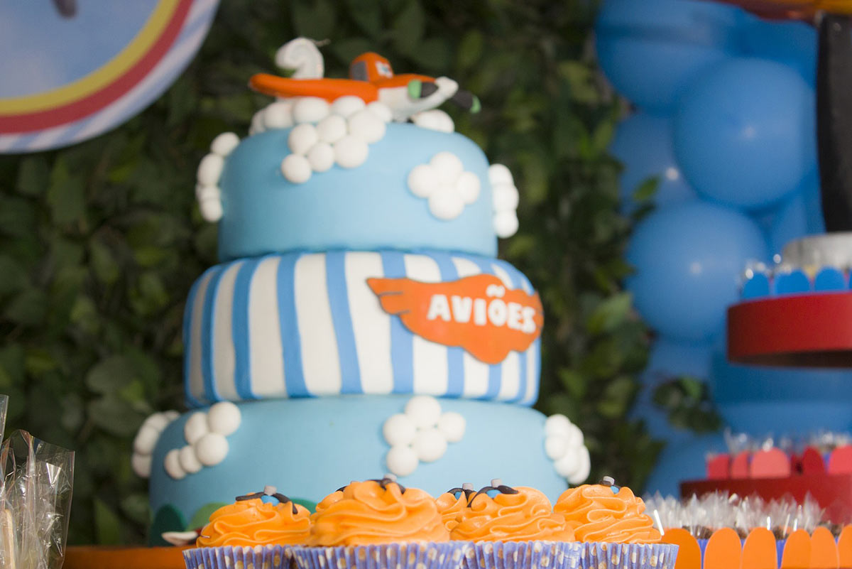 Three-tiered blue cake with an orange airplane on top.