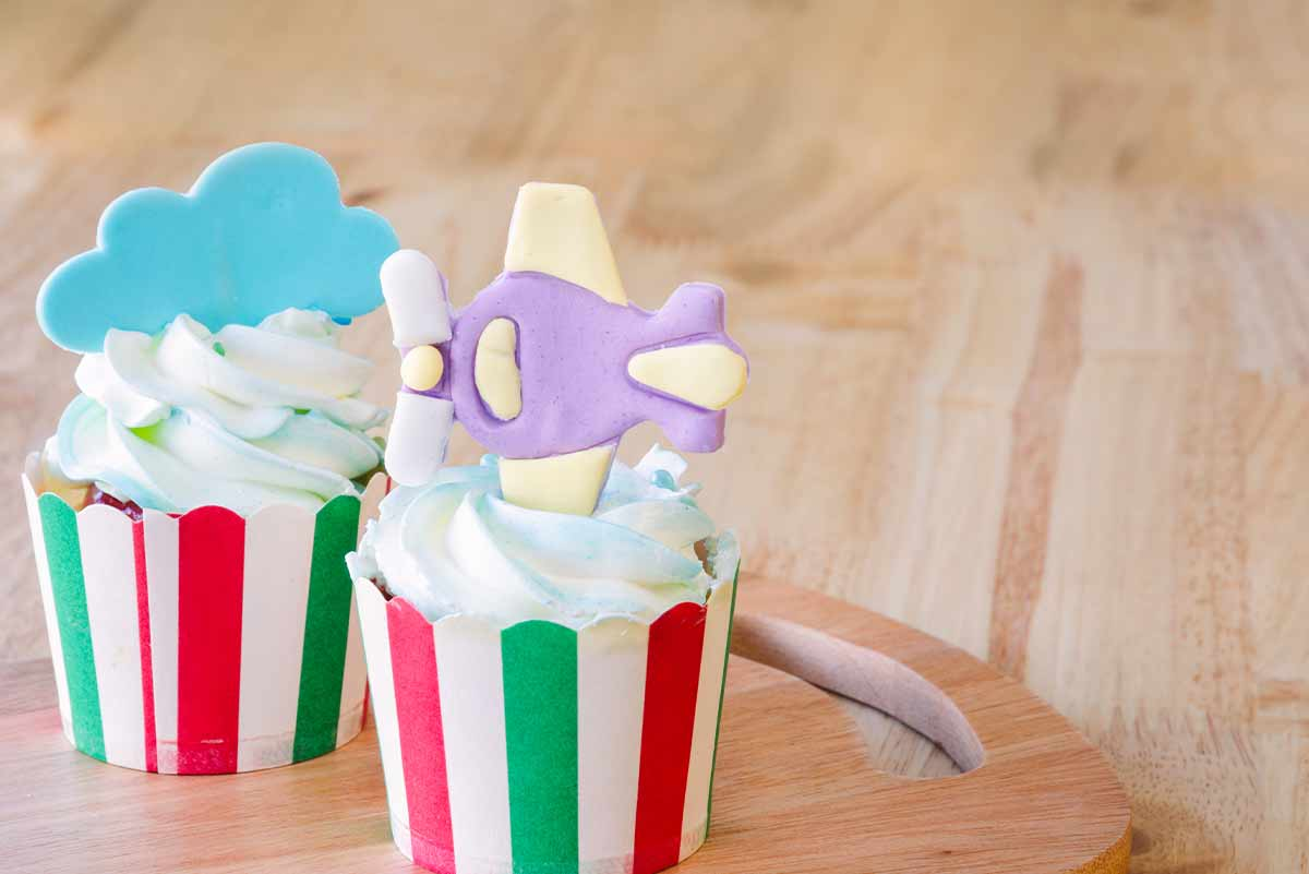 Cupcakes with a decorative, icing airplane stuck in one and an icing cloud in the other.