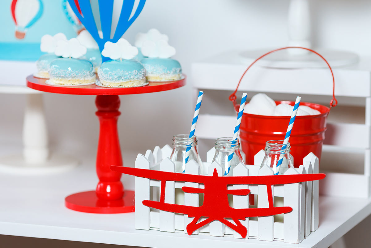 Platter of blue, sky-themed cakes and red airplane decorations around the table.