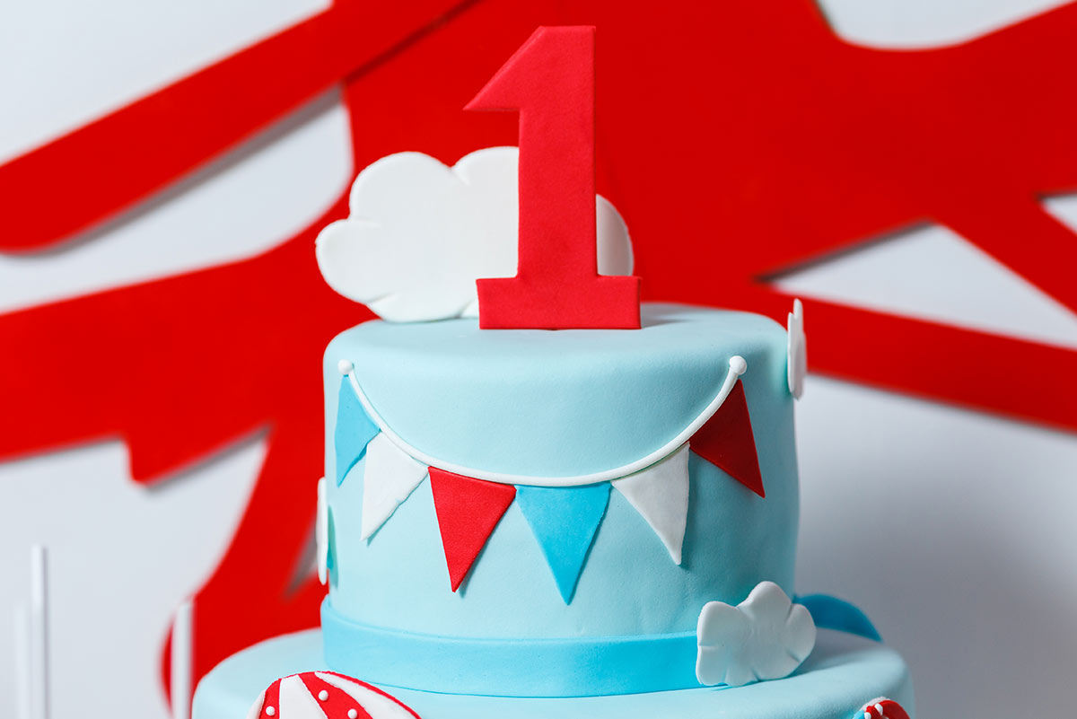 Blue, tiered first birthday cake with a big, red airplane decoration on the wall behind.