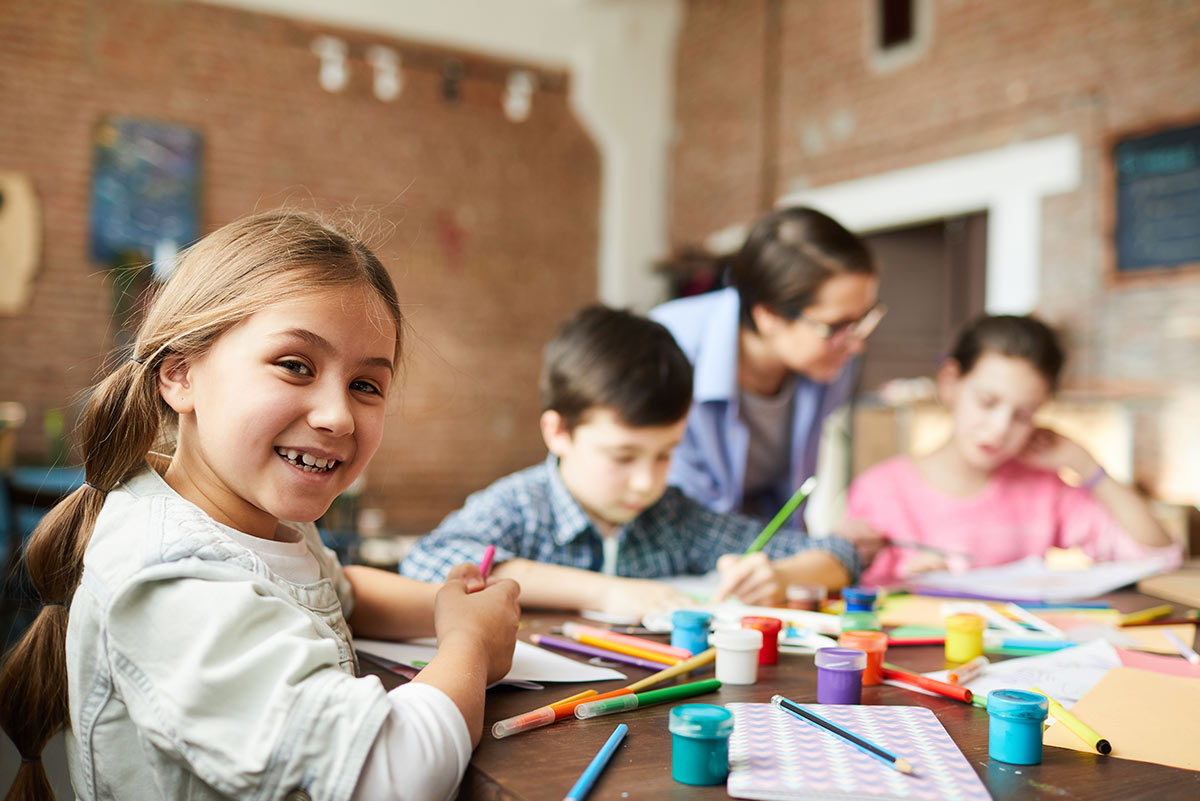 Kids sat at a table doing crafts to make a DIY chore chat, focus on one girl who is smiling.