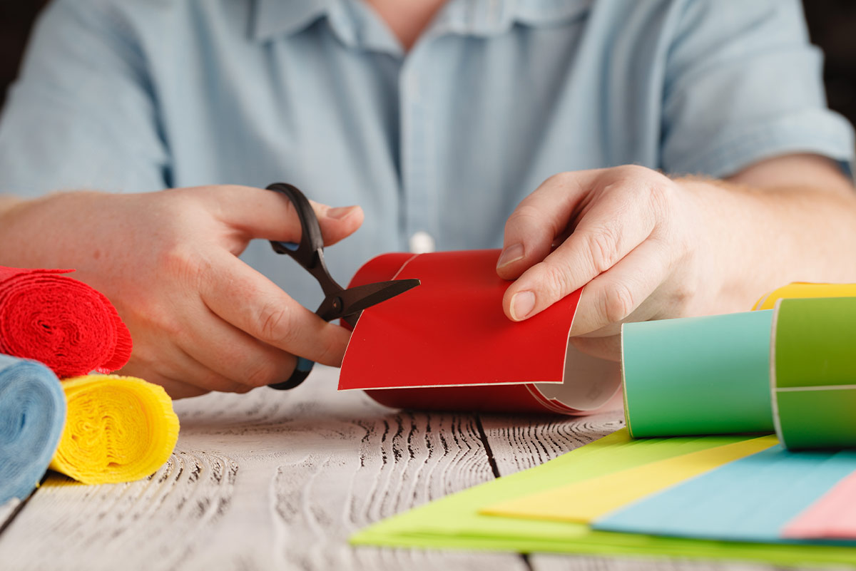 Close up of someone cutting a piece of red card to make a DIY chore chart.