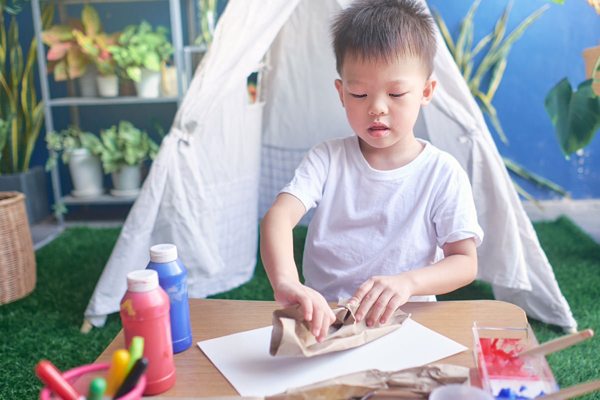 Young boy sat by a table in front of a living-room tent making a DIY chore chart.
