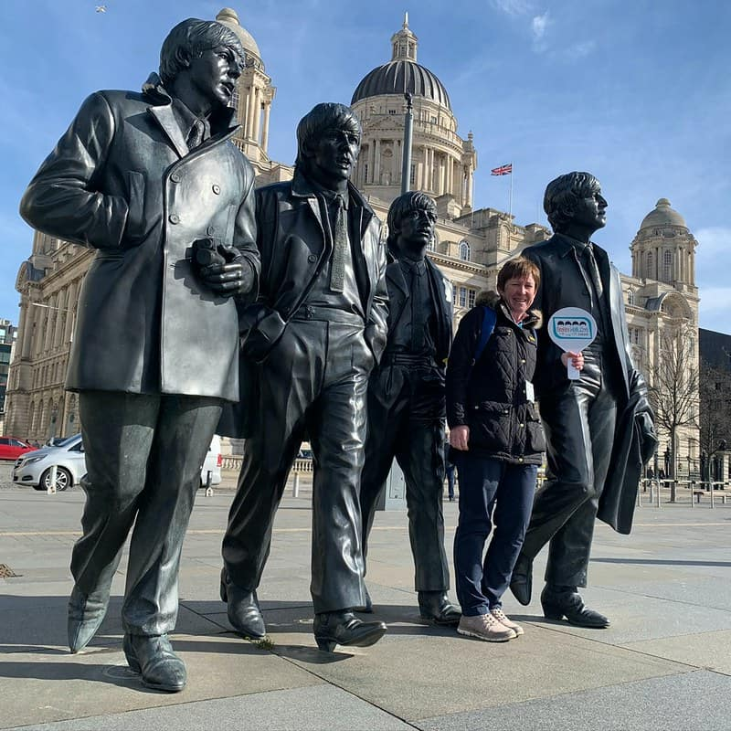 Someone posing with a statue of The Beatles walking through Liverpool.