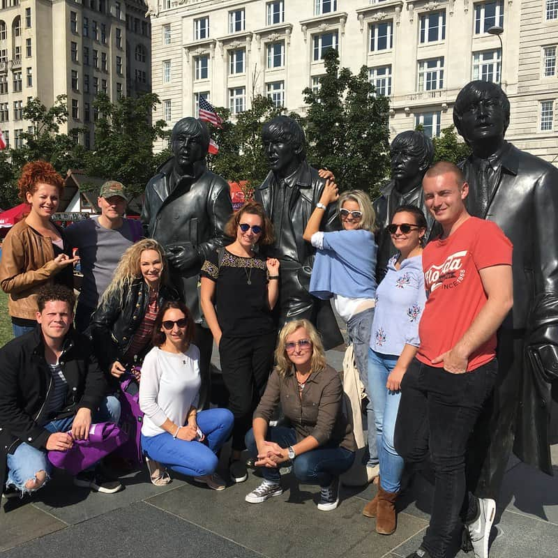 People posing with statues of The Beatles in Liverpool.