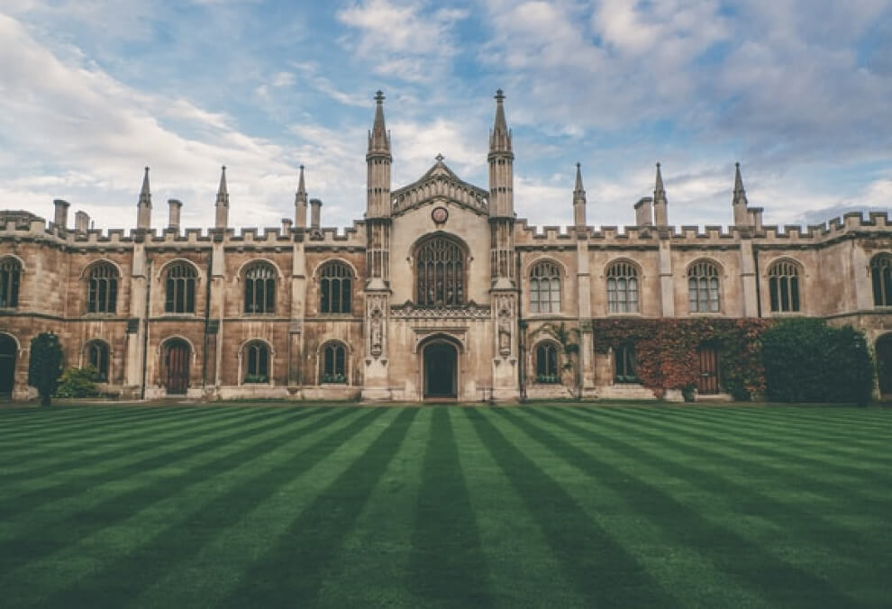 Oxford University building set perfectly in the centre of a carefully manicured lawn.