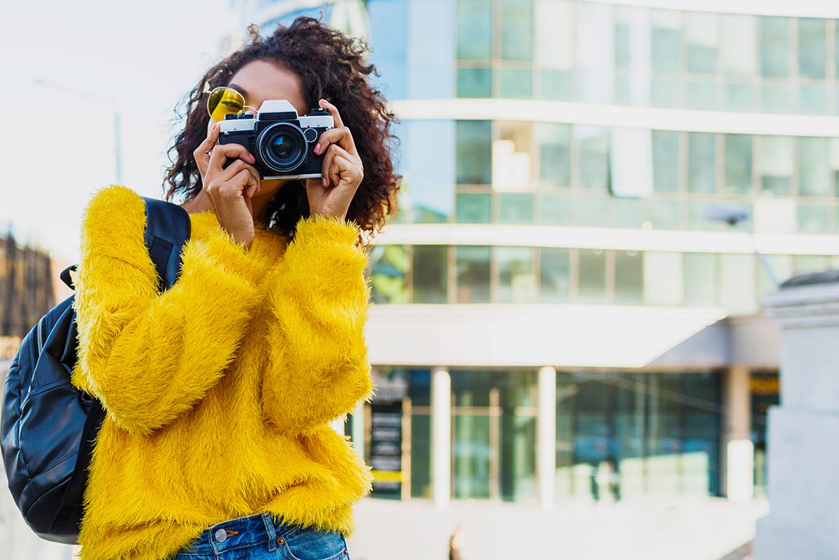 Teenage girl in a yellow jumping holding a camera up to her face taking a photo.