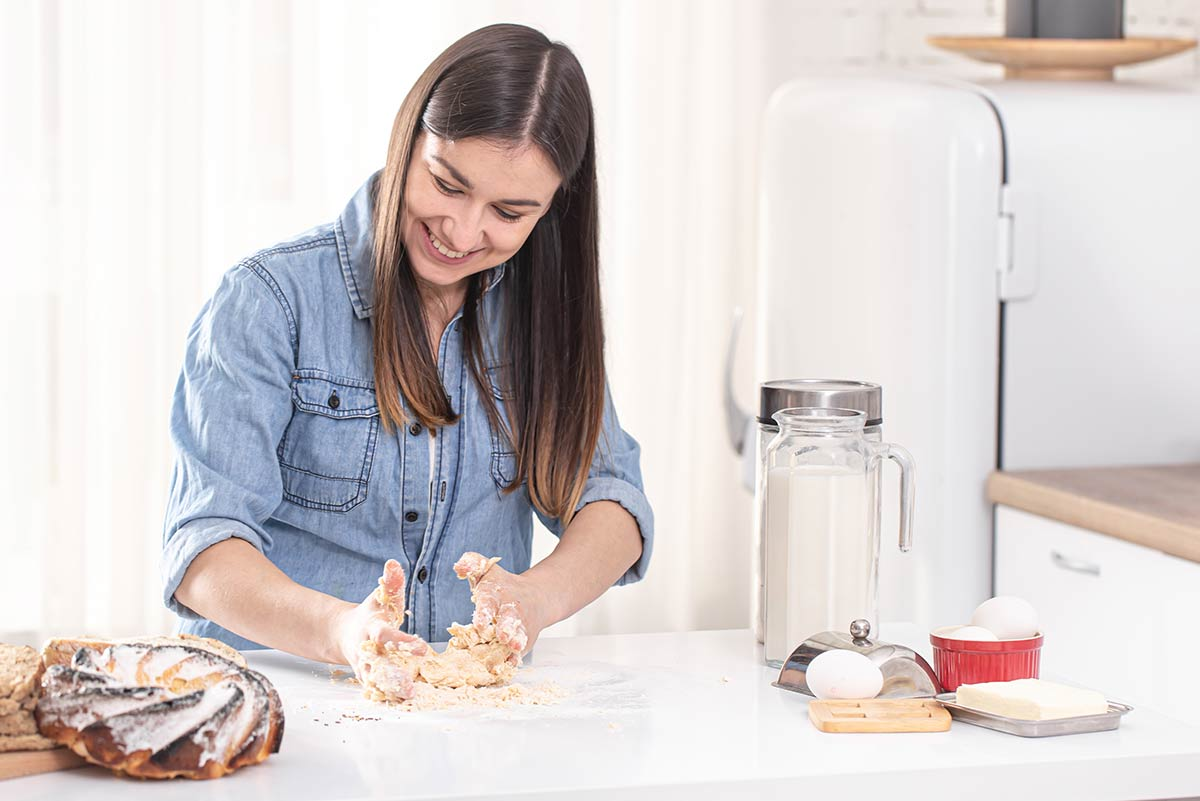 Woman smiling as she kneads dough with her hands on the kitchen counter.