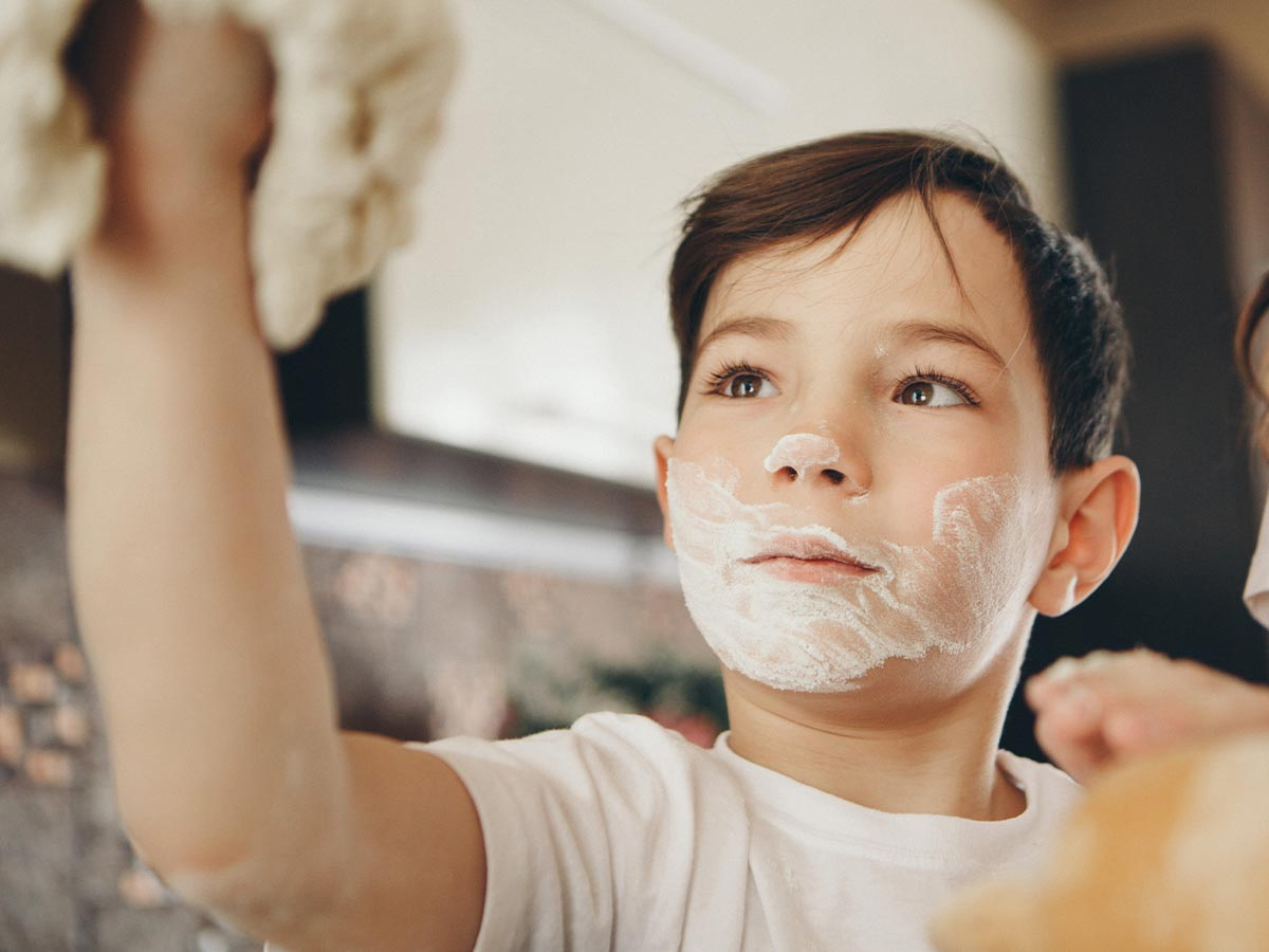 Young boy holding dough in the air with a beard of flour on his face.
