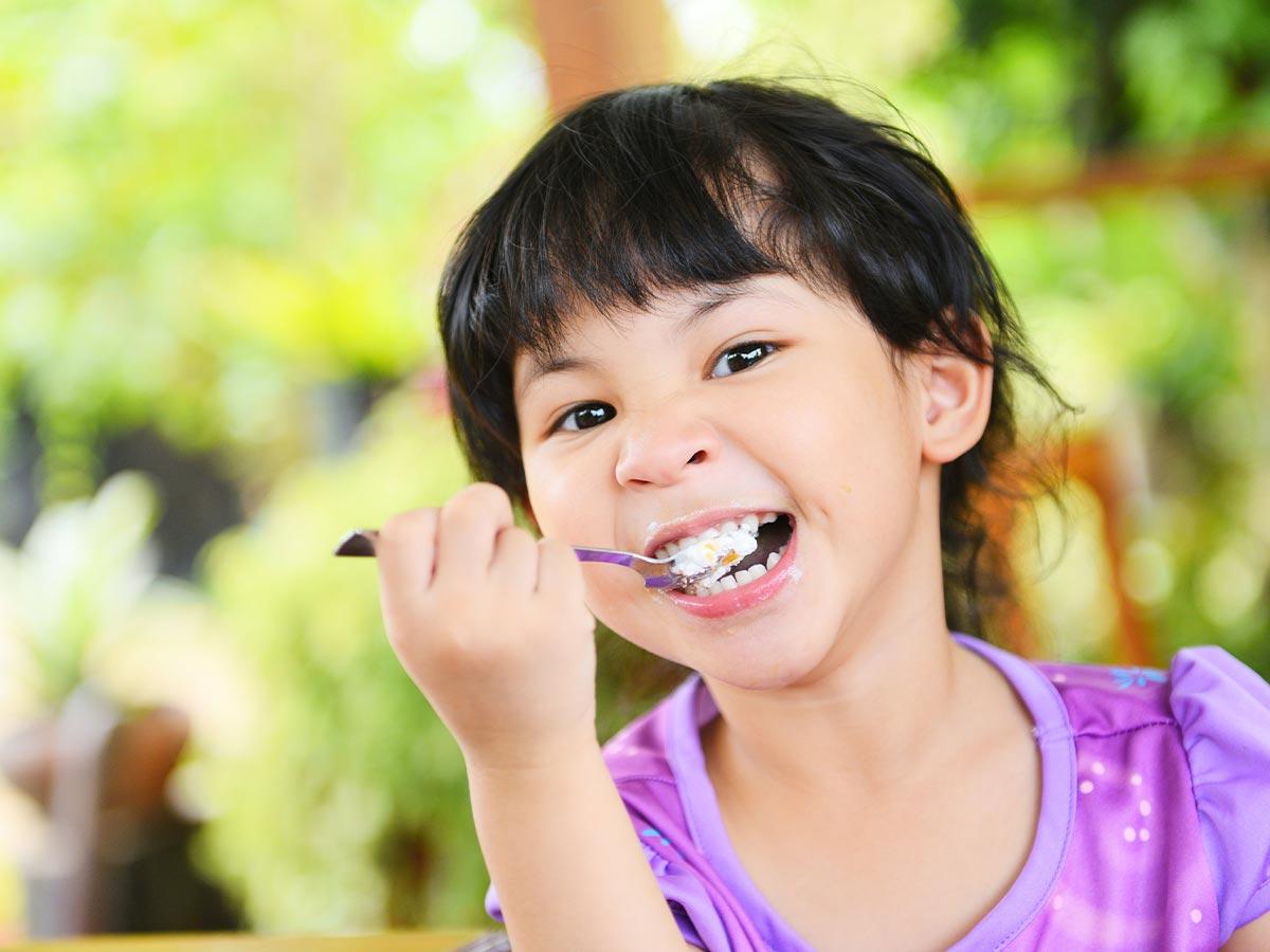 Girl wearing purple t shirt eating a piece of tardis cake in the garden.