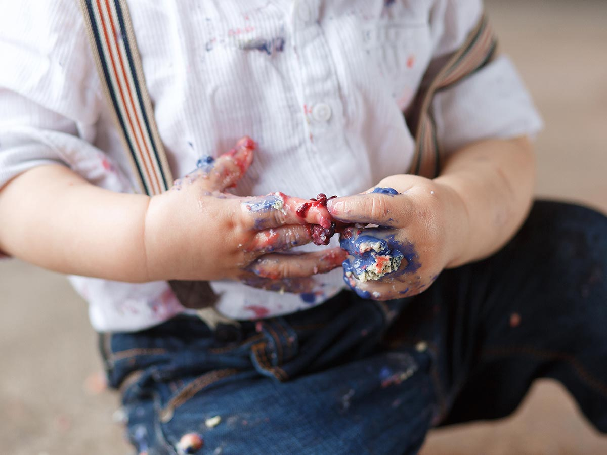 Close up of little boy's hand which are covered in blue and red icing.
