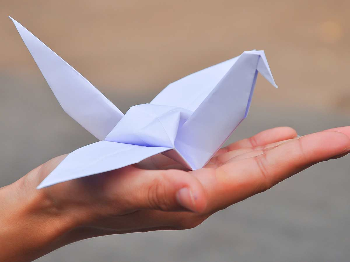 Hand holding a white origami eagle in its palm.