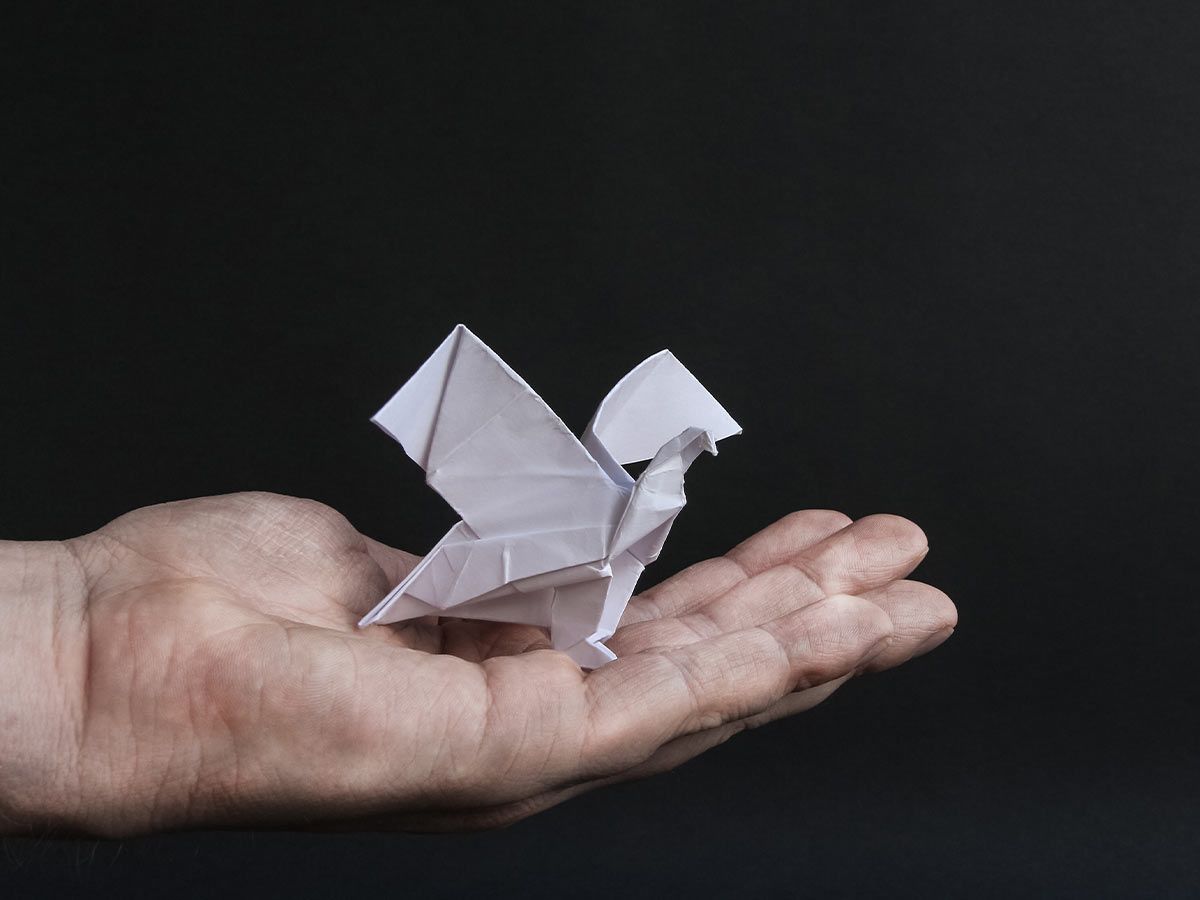 A white origami eagle in the open palm of a hand against a black background.