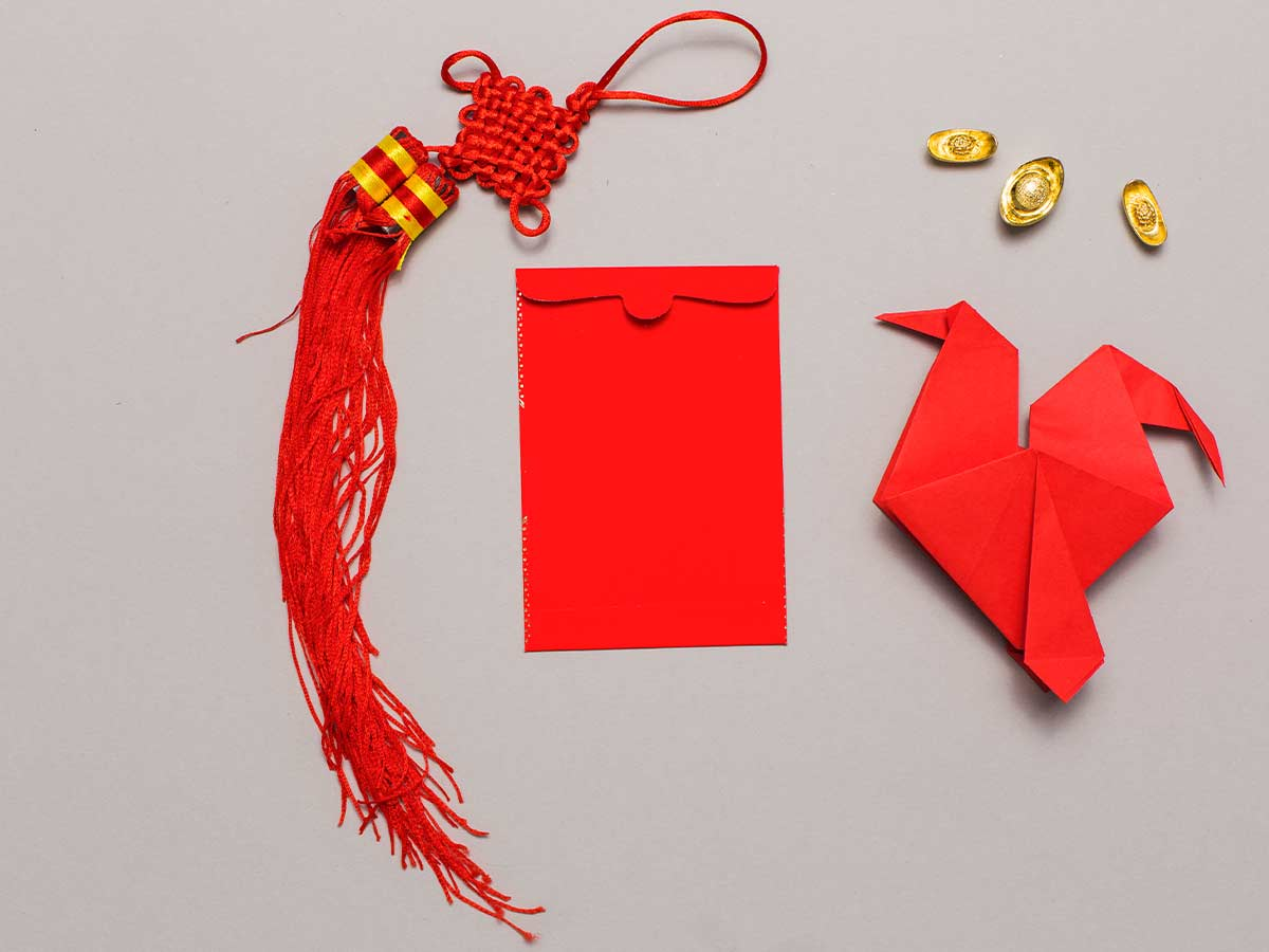 Red origami eagle on the surface next to a red envelope and tassel.