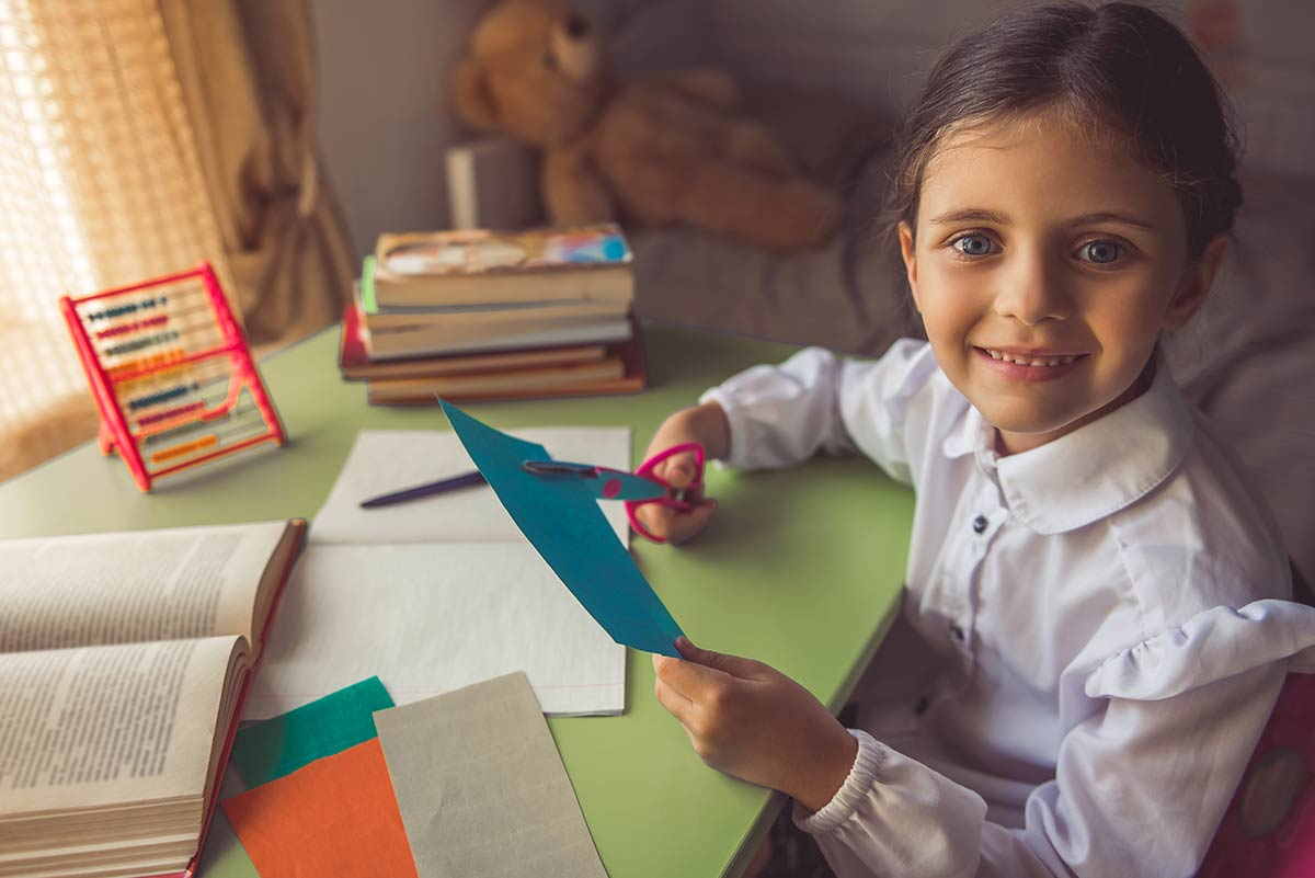 Blue-eyed young girl sat at a table smiling as she cuts paper to make an origami swallow.