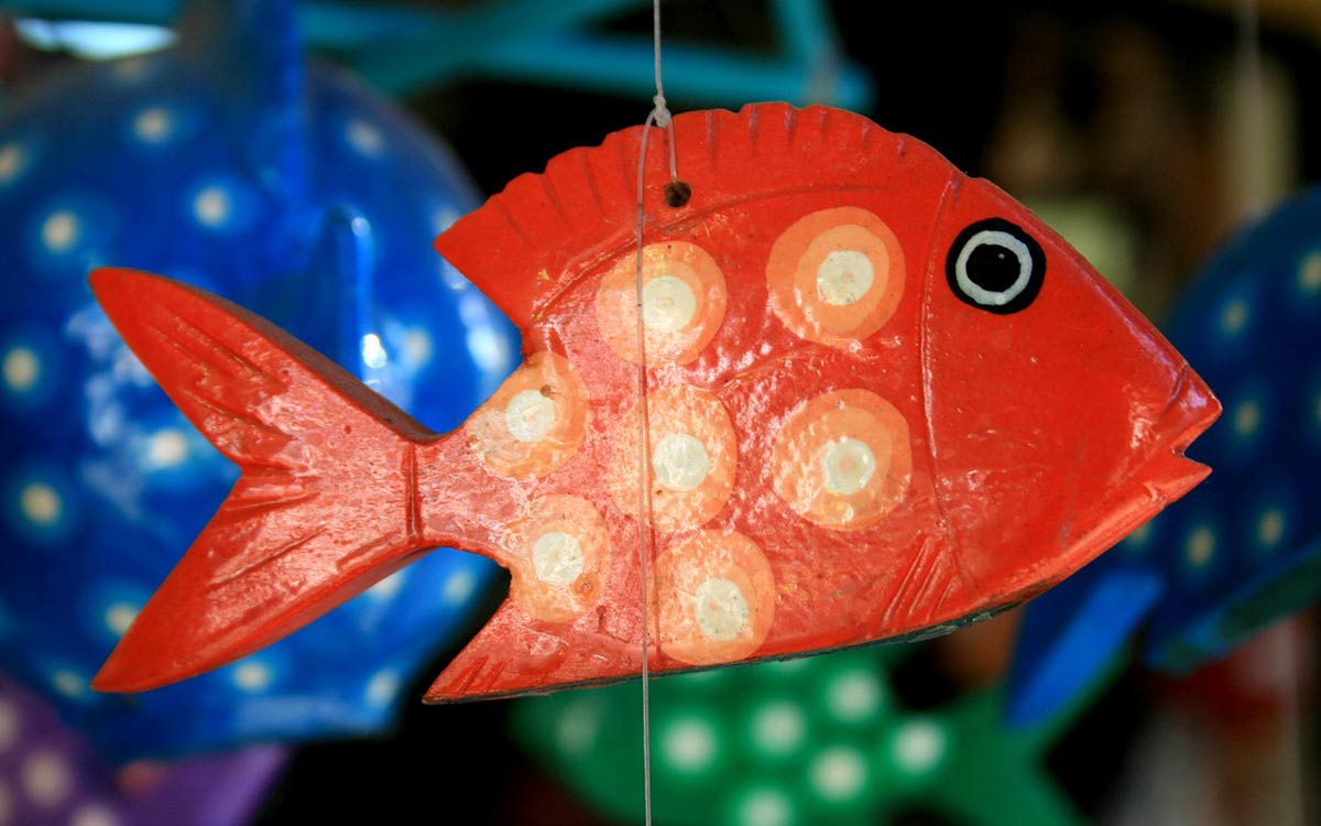 Red paper mache fish hanging from a string.