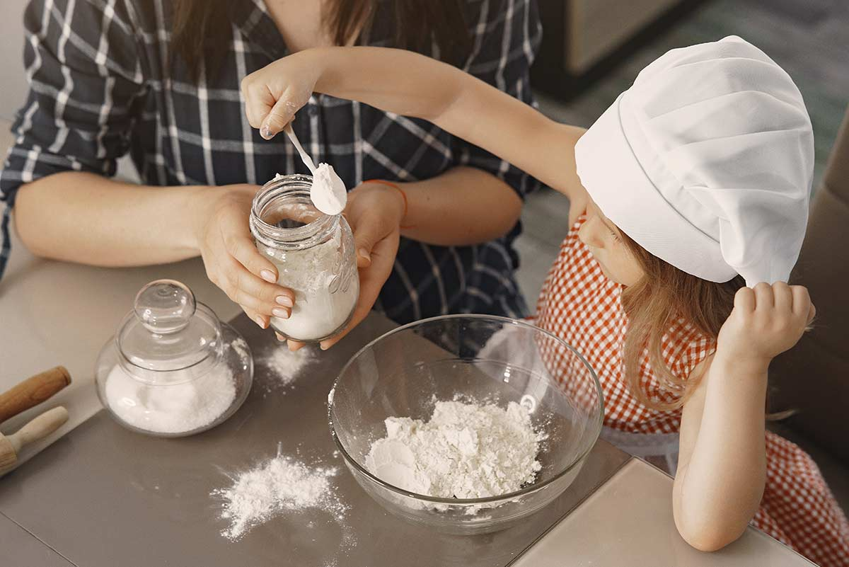 Young girl in a chef's hat adding a spoon of flour into her cake mix from the jar that her mum is holding for her.