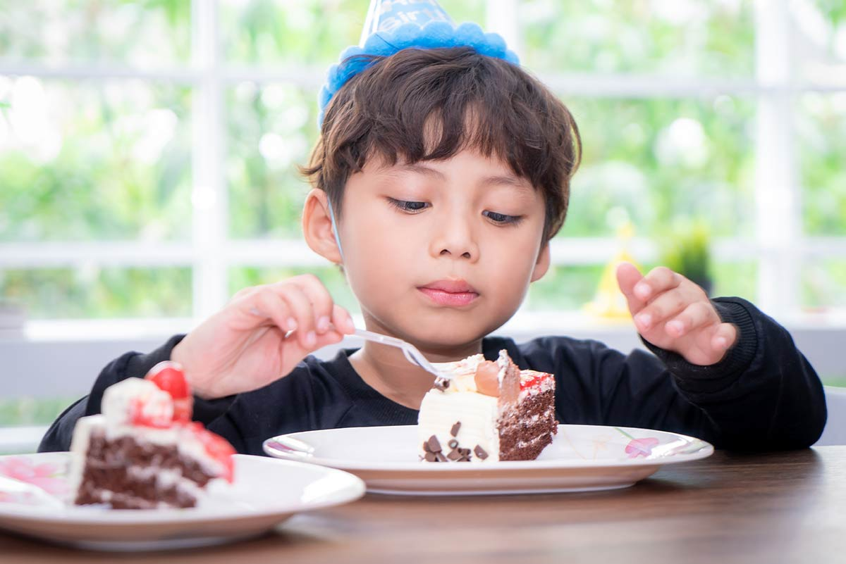 Young boy wearing a blue party hat sat at the table eating a piece of cake.