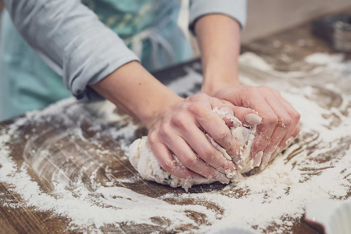 Close up of a woman kneading dough on the kitchen worktop.
