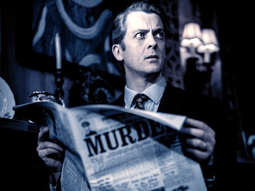 Black and white photo of an actor in The Mousetrap holding a newspaper.