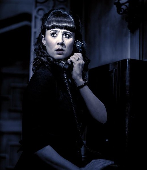 Black and white photo of an actress in The Mousetrap on the phone.