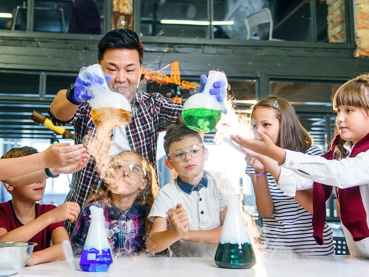 Teacher showing young kids science experiments with colourful liquids in flasks.