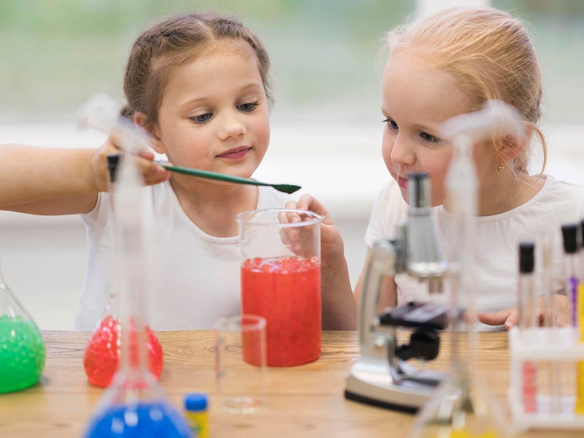 Two preschooler girls doing science experiments.