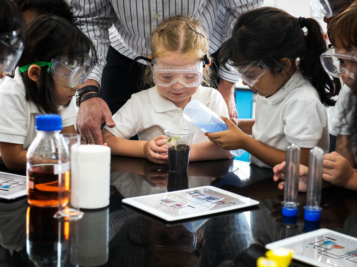 Preschoolers sat at a table wearing goggles while doing science experiments.