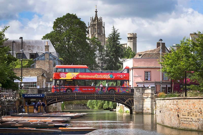 An open-air City Sightseeing bus driving over a bridge in Cambridge.