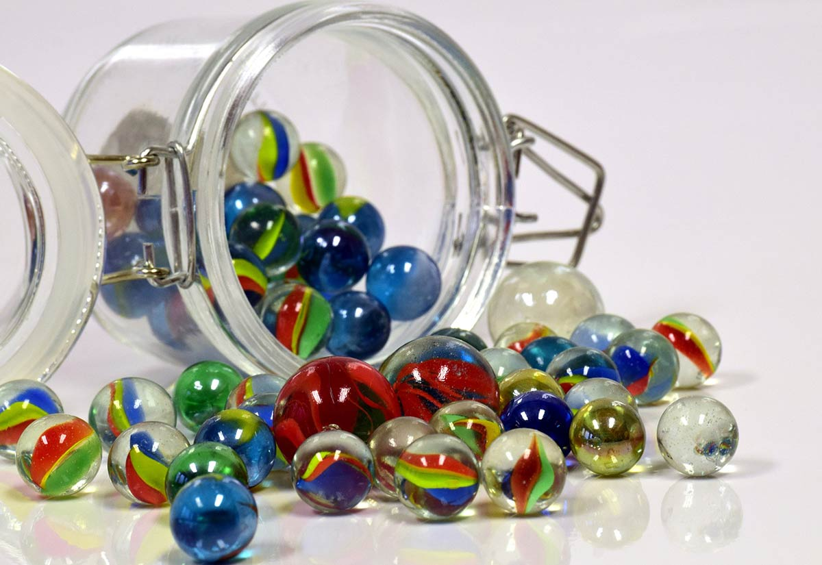 Jar of colourful marbles tipped over, the marbles spilling out.